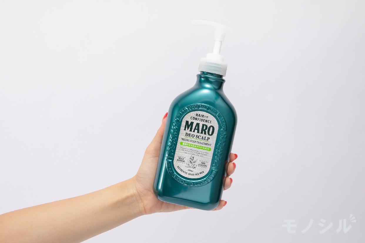 MARO(マーロ) 薬用 デオスカルプ トリートメントの女性が手で持ちサイズ・容量を検証している様子