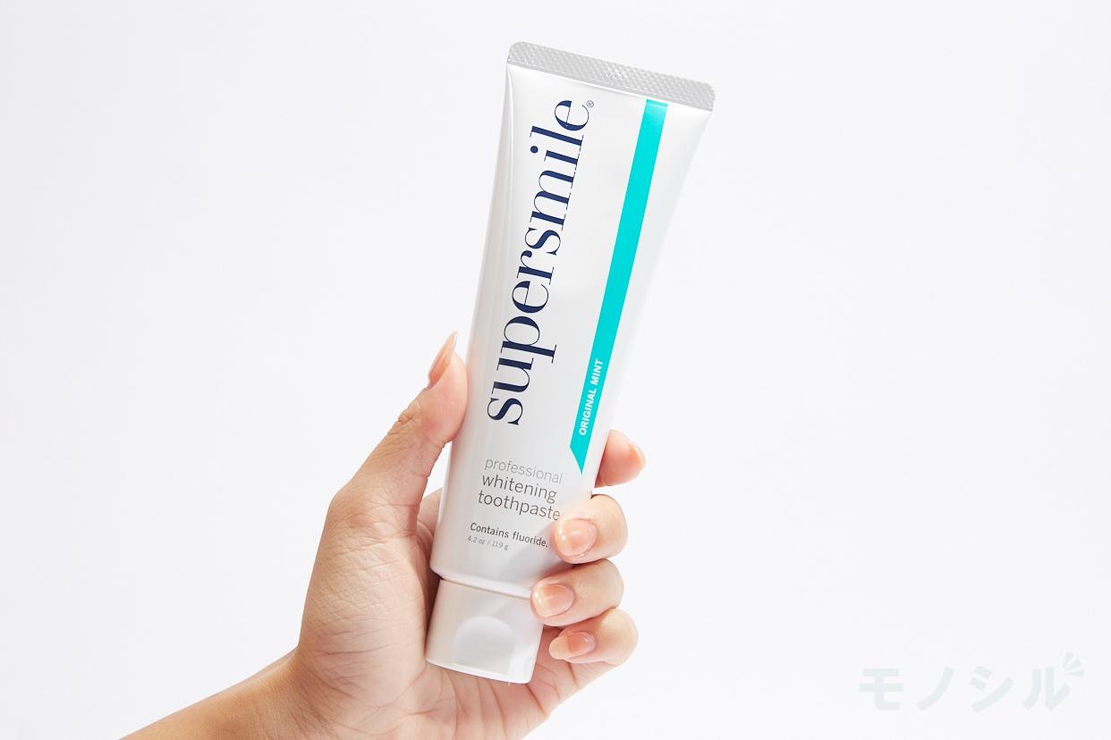 supersmile(スーパースマイル)薬用ホワイトニング歯磨きの手に持った商品